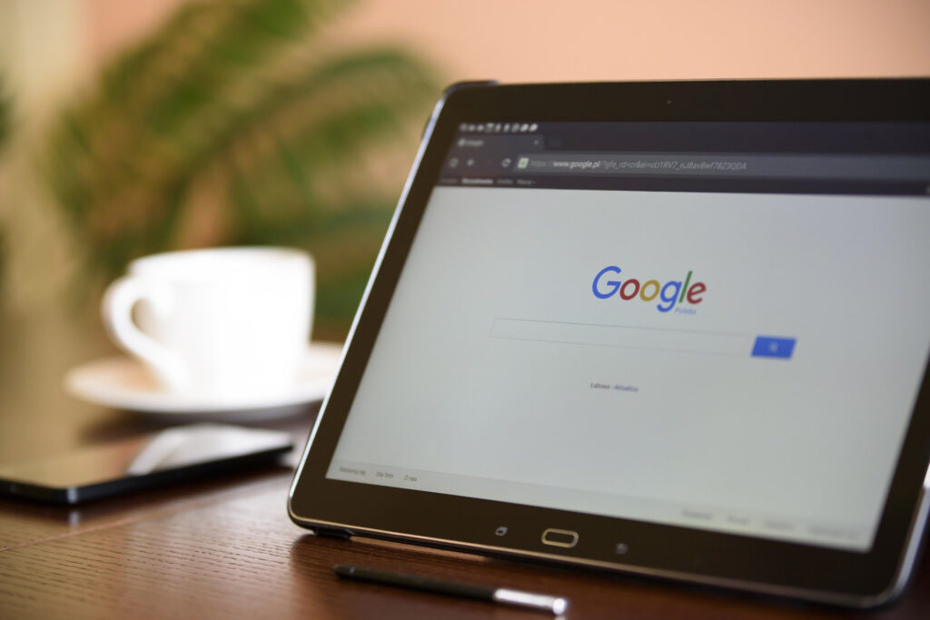 a Google screen on a tablet next to a white coffee cup