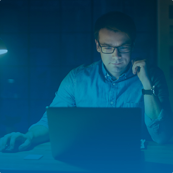 a man in a blue shirt working on a black laptop