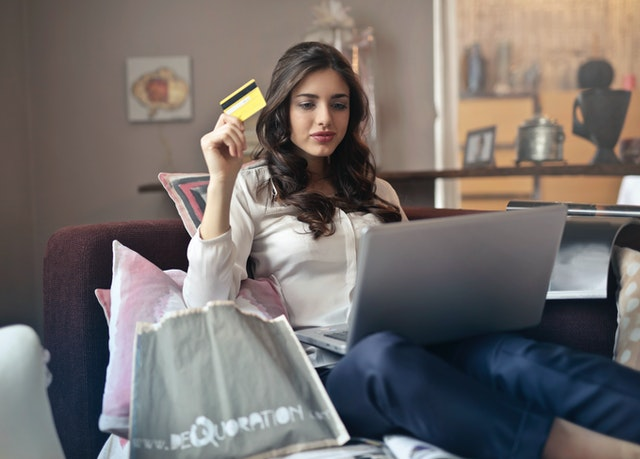 A woman holds a credit card while shopping online.
