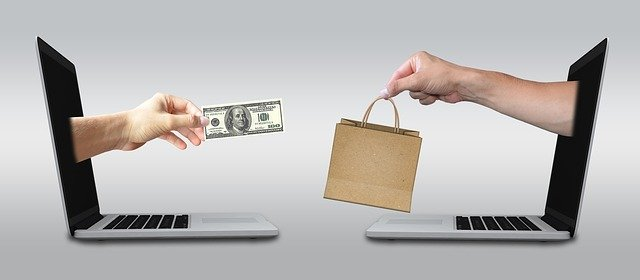 two laptops with hands exchanging cash for a shopping bag