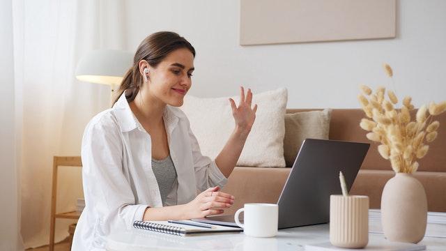 woman waves in laptop video