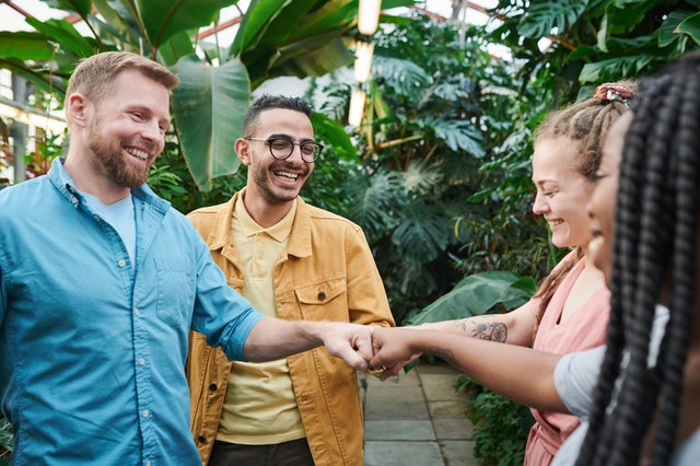 Four people smiling and fist bumping