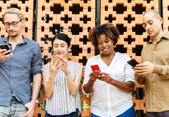 four people looking at mobile phones