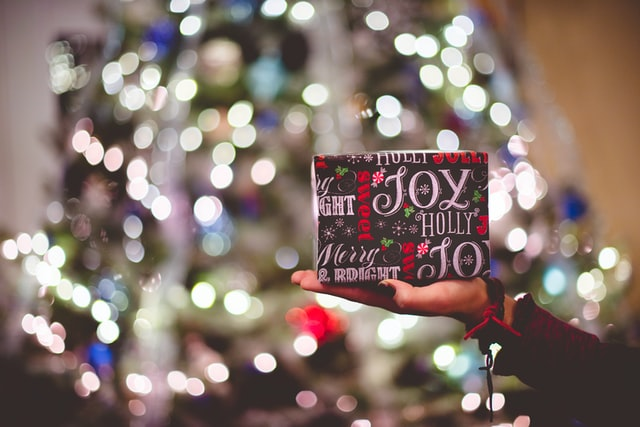 Gift with joy wrapping paper against a Christmas tree background