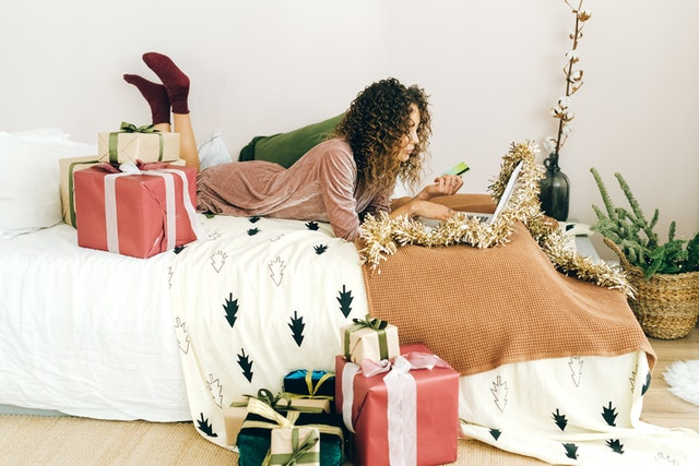 woman on bed with gifts, shopping on her laptop