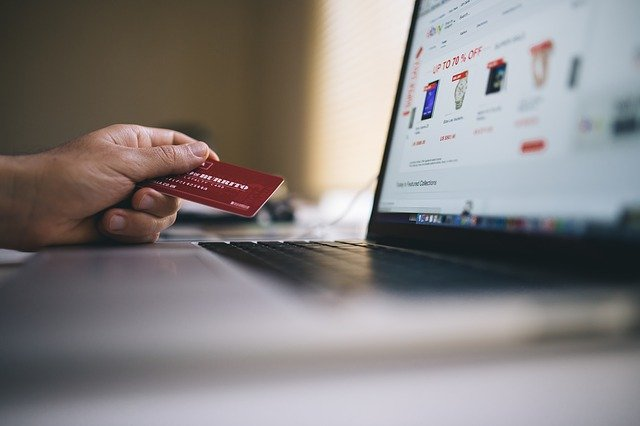 A person shopping online with their credit card