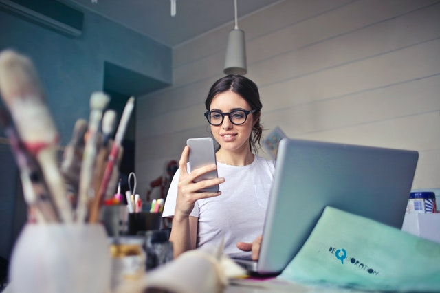 A young woman sitting in an art studio looking at her smartphone.